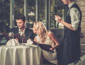 Cheerful couple with menu in a restaurant making order — Stock Photo