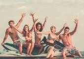 Group of happy multi ethnic friends sitting on a jet ski — Stock Photo