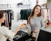 Happy woman paying with credit card in fashion showroom — Stock Photo