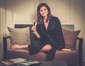 Woman in bathrobe relaxing with glass of champagne in hotel room — Zdjęcie stockowe
