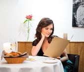 Beautiful young lady choosing food in restaurant  — Stock Photo