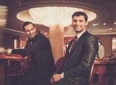 Two fashionable men behind table in a casino — Stok fotoğraf