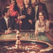 Group of stylish people playing in a casino — Stock Photo #61550973