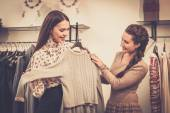 Young woman choosing clothes on a rack in a showroom  — Stock Photo