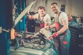 Two mechanics adding oil level — Stock Photo