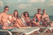 Group of multi ethnic friends with drinks on a beach — Stock Photo