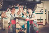 Mechanics changing oil  in a car workshop — Stockfoto