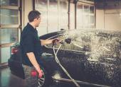 Worker washing luxury car on a car wash — Stock Photo