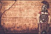 Roman legionary soldier in front of  wall — Stock Photo