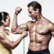 Woman measuring athletic's man biceps — Stock Photo #62694193