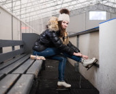 Cheerful girl putting on skates — Stockfoto