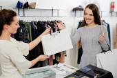 Customer with shopping bag in fashion showroom — Stock Photo