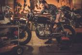 Mechanic and vintage style cafe-racer motorcycle — Stock Photo