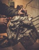 Mechanic working with with motorcycle engine — Stock Photo