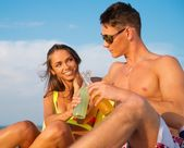 Couple relaxing on a deck chairs on a beach — Stock Photo