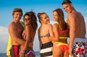 Multi-etnische vrienden met dranken ontspannen op een strand — Stockfoto