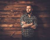 Man in checkered shirt, wooden house interior — Stock Photo
