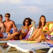 Group of multi ethnic friends with drinks relaxing on a beach — Stock Photo #66266389