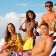 Group of multi ethnic friends with drinks relaxing on a beach — Stock Photo #66266463