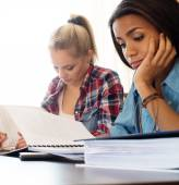 Girls students preparing for exams in apartment interior behind table  — Stock Photo