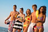 Group of multi ethnic friends walking on a beach — Stock Photo