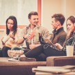 Group of cheerful students with drinks and popcorn in home interior — Stock Photo #68252319