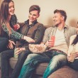 Group of cheerful students with drinks and popcorn in home interior — Stock Photo #68252329