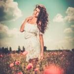 Girl wearing white summer dress in poppy filed — Stock Photo #68252939