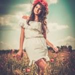 Girl wearing white summer dress in poppy filed — Stock Photo #68252947