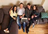 Cheerful students with laptop and drinks on a sofa — Stock Photo