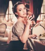 Jovem mulher com um copo de vinho tinto sozinho em um restaurante — Fotografia Stock