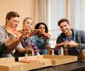 Group of multi-ethnic friends with pizza and bottles of drinks having party — Stock Photo