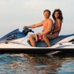Multi ethnic couple sitting on a jet ski — Stock Photo #68360527