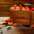 Wooden crate with tasty tangerines on a table — Stock Photo #68360847