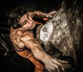 Muscular man practicing rock-climbing on a rock wall indoors  — 图库照片