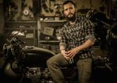 Rider and his vintage style cafe-racer motorcycle in customs garage  — Stock Photo