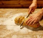 Man cutting homemade bread  on a table — Stock Photo