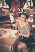 Beautiful young girl in luxury restaurant interior — Stock Photo