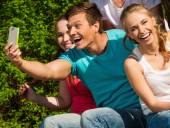 Sporty teenage friends in a park taking selfie — Stockfoto