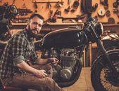 Mechanic building vintage style cafe-racer motorcycle  in custom garage — Stock Photo