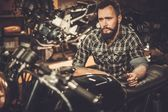 Mechanic building vintage style cafe-racer motorcycle  in custom garage — Stock Photo