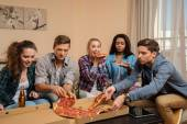 Group of young multi-ethnic friends with pizza and bottles of drink celebrating in home interior — Stock Photo