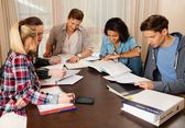 Multi ethnic group of students preparing for exams in home interior behind table  — Stock Photo
