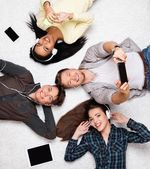 Friends relaxing on a carpet with gadgets — Stock Photo