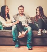 Cheerful multi-ethnic friends sitting on a sofa — Stock Photo