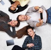 Happy multiracial friends relaxing on a carpet with gadgets — Stock Photo