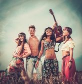 Multinational hippie friends with guitar in a wheat field  — Stock fotografie