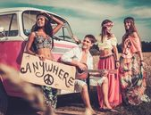 Multinational hippie hitchhikers with guitar and luggage on a road — Stock fotografie