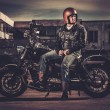 Biker and his bobber style motorcycle on a city streets — Stock Photo #70888869