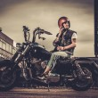 Biker and his bobber style motorcycle on a city streets  — Stock Photo #70888887
